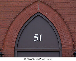 the number fifty one in metal numbers on archway above door, surrounded by bricks, easthampton massachusetts