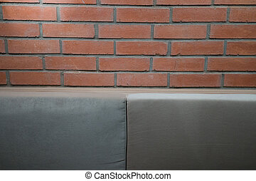 Brick background with soft lighting and furniture details.