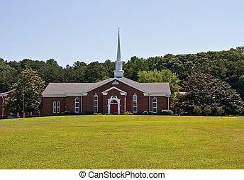 Brick Church with Red Door Past Green Grass
