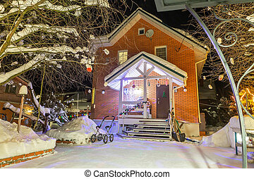 brick cottage in the winter forest. Backyard. there is a stroller at the house. Snow on the paths of the house.