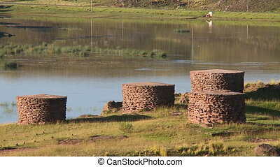 Brick Cylinders Next to Water - Steady, medium wide shot of...