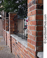 Brick Fence - Brick and wrought-iron fence decorated with...
