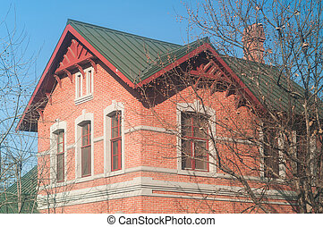 Brick house building in winter with tree branch in fall season