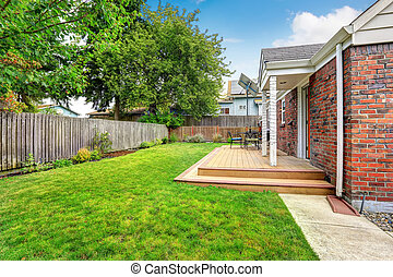 Brick house exterior with walkout wooden deck and green lawn