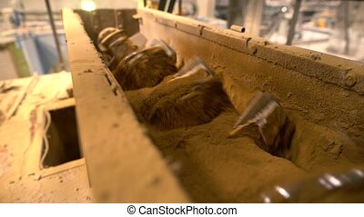 Brick industry. Transportation of sand using screw, close-up view