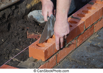 Brick layer  - Bricklayer using trowel to tap a brick level