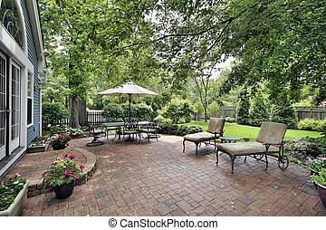 Brick patio of suburban home - Brick patio with table...