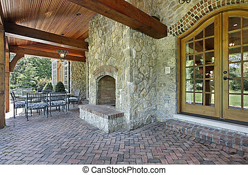 Brick patio with stone fireplace