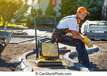 Brick Paver Worker Resting on His Soil Plate Compactor While...