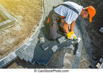 Brick Paving Works. Professional Caucasian Worker Building...