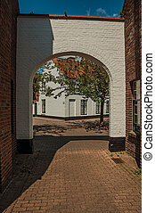 Brick portal to enter a graceful square with tree and old brick houses at Bruges.