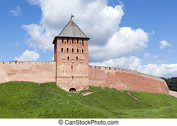 brick tower and wall of Novgorod Kremlin, a medieval fortress, grass, sky with clouds