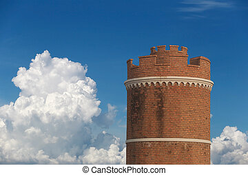 Brick tower on blue sky background.