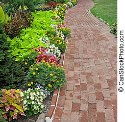 Winding red brick walkway in garden.