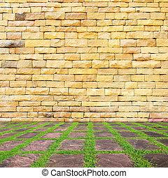 brick wall and green grass ground.
