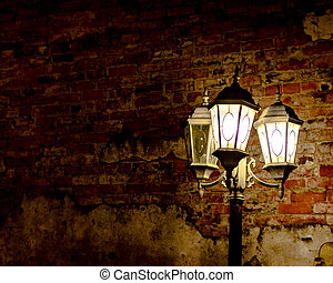 Brick wall background with illuminated street lamp