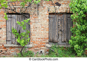 brick wall with wooden windows frames of the old house