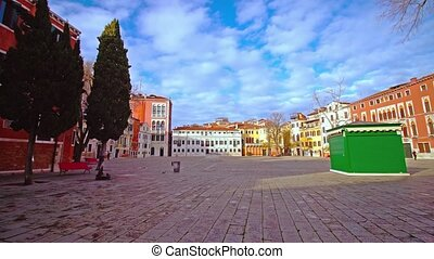Wide bricked square with colorful buildings and lonely passers-by against cloudy blue sky on sunny day in Italian Venice city