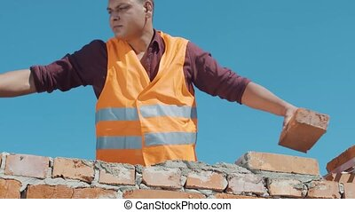 Bricklayer build wall on a blue sky background.