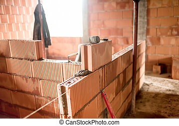 bricklayer building new house with brick walls, interior rooms
