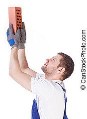 Bricklayer giving a brick
