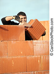 bricklayer in construction site erecting red brick wall