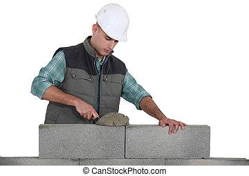 Bricklayer laying blocks