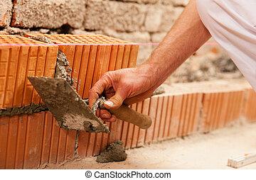 bricklayer making wall with brick