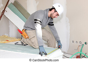 Bricklayer measuring plasterboard