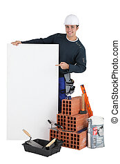 Bricklayer posing with his building materials and a blank sign