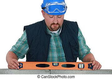 bricklayer taking measurements