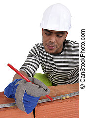 Bricklayer using a steel measure
