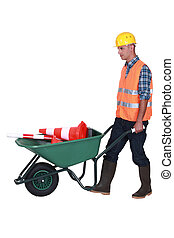 bricklayer with wheelbarrow and construction cone
