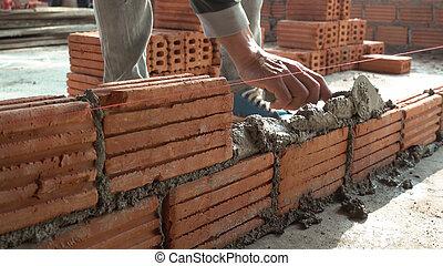 Bricklayer worker installing brick masonry on exterior wall