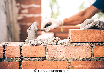 Bricklayer worker installing brick masonry on exterior wall...