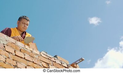 Bricklayer working on a blue sky background.