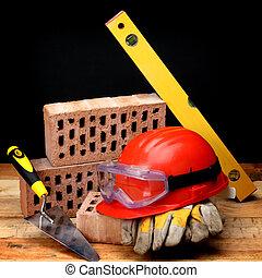 Bricks, trowel and helmet on work place