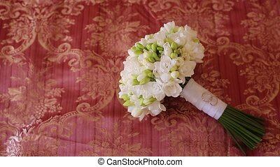 Bridal bouquet and wedding rings on red background