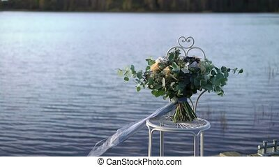 Bridal bouquet near lake outdoors