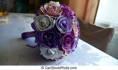 bridal bouquet of blue, video purple and white roses on a table
