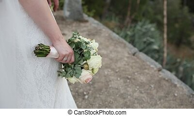 Bridal bouquet of roses and eucalyptus in the hands of the...