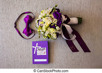 bridal bouquet of white and blue flowers, rings, purple butterfly and invitation-cards lie on a light background, preparations for the wedding, the groom's fees, dress, wedding attributes