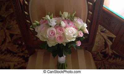Bridal bouquet of white and pink roses on chair