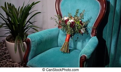 Bridal bouquet on blue chair in room