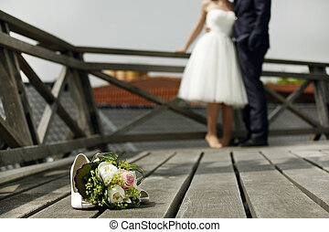 Bridal bouquet with bride and groom on a wooden deck