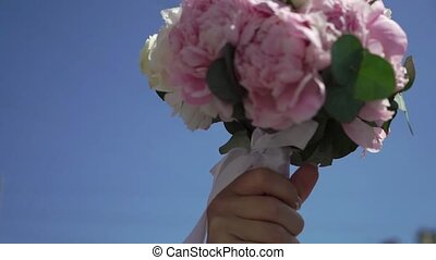 Bridal bouquet with pink flowers at sunny day