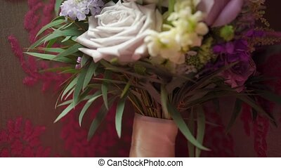 Bridal bouquet with pink, white and violet roses at pink...