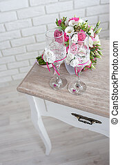 bridal bouquet with wedding rings and wine glasses on the table in the morning of the day