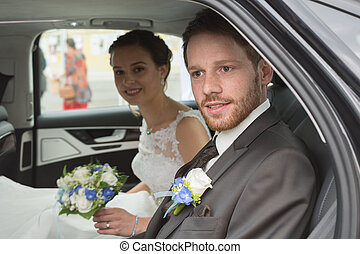 Bridal couple in the wedding car