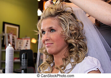 A young attractive bride getting her hair done on her wedding day.